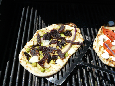 Moving grilled pizza with wide fish spatula